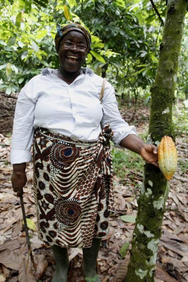 Frau neben einem Kakaobaum mit einer Kakaofrucht