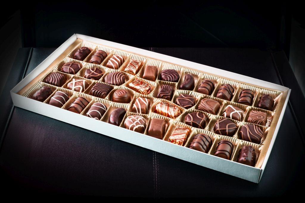 Eine Schokoladen-Pralinen Schachtel auf einer Ledercouch
